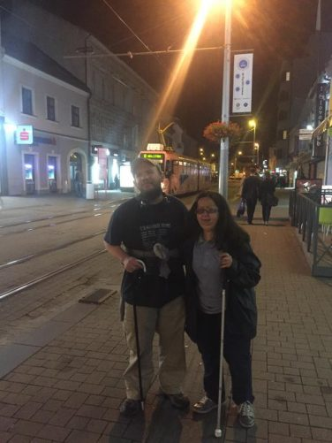 Tony and Tatiana on Obchodna street. An orange coloured tram approaching behind.