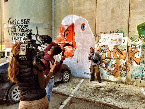 Almudena filming Tony having his photo taken by some of the artwork on the border wall. Tony is stand next to a large mural of a goose's head.