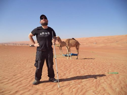 Tony and two more camels in the desert. The reddish coloured desert sand extending off to the horizon.