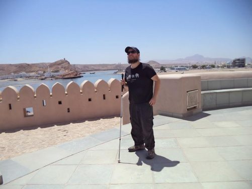 Tony standing on a circular raised paved area with a view towards the harbour in the city of Sur. Ayjah Lighthouse is out of view in the middle.