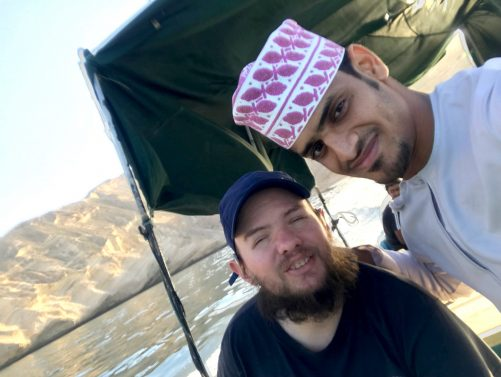 Tony and a local Omani guy named Ahmed on board a speedboat made of wood.