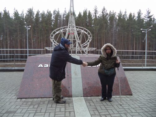 At the dividing line monument. Tony and Tatiana holding hands while standing on opposite sides of the dividing line. Tony on the left in Asia and Tatiana on the right in Europe.