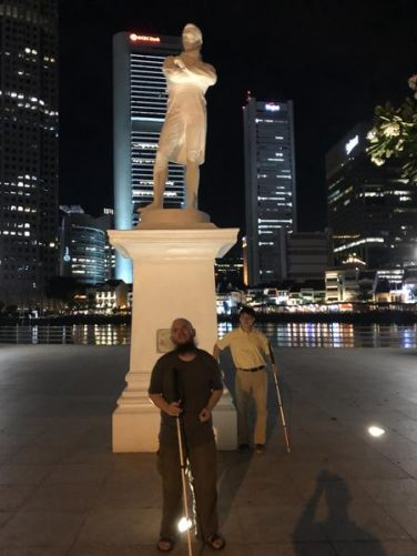 Tony and Johnny by a large statue of Sir Stamford Raffles (1781-1826), who established a British trading post in Singapore in 1819.