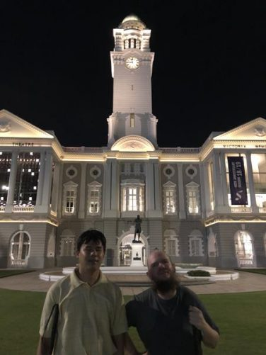 Tony and Johnny in front of the Victoria Memorial Hall at Empress Place. This theatre and concert hall was built between 1855 and 1909 in neoclassical style. The central clock tower is in view. A Sir Stamford Raffles statue stands in front. This is the same as the statue at Raffles Landing Site, with this being the original in bronze. It was unveiled in 1887.