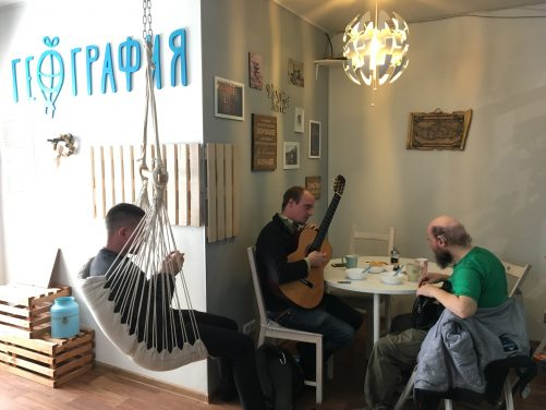 Tony sitting at a table in the kitchen in Geo Hostel with a local guy named Sergy. He's holding and playing a guitar. Another guy is sitting in a hammock seat. He is a traveller from the US. Bowls and cups on the table, the products of breakfast.