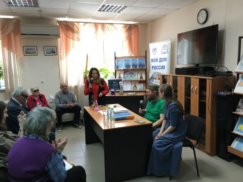 Tony sitting at a table holding a microphone talking to a group of local people, most of whom, are blind/visually impaired and/or partially deaf. A Russian woman along side also holding a microphone. She is interpreting for the audience. Tony is wearing a traditional Tatar hat. It is round and colourful. The location is the library for the blind and visually impaired.