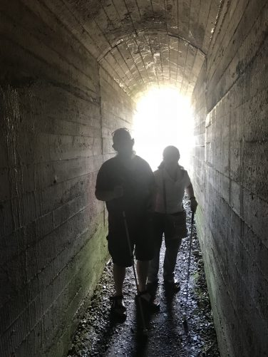 Tony and Tatiana walking along a narrow passageway with concrete walls inside one of the bunkers. Military personnel lived inside these bunkers and slept in hammocks attached to the walls. There were up to 40 men in each bunker.