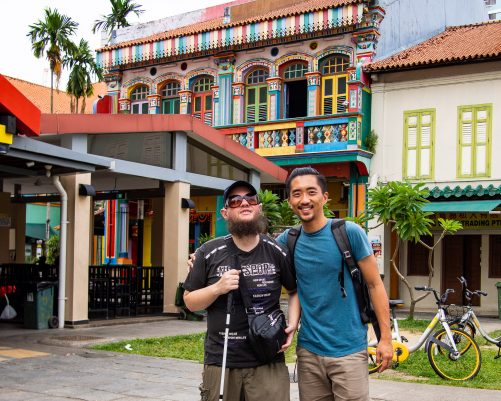 Tony and Royden with colonial era two-storey buildings in the background. One is brightly painted with a balcony. Along one of the main streets of Little India.