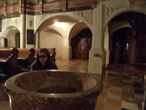 Tatiana next to a marble font inside Graz Cathedral.