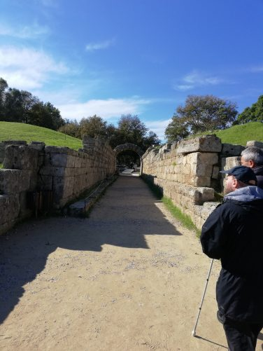 A sunken walkway lined with stone walls. This leads from the ancient Olympic Stadium.