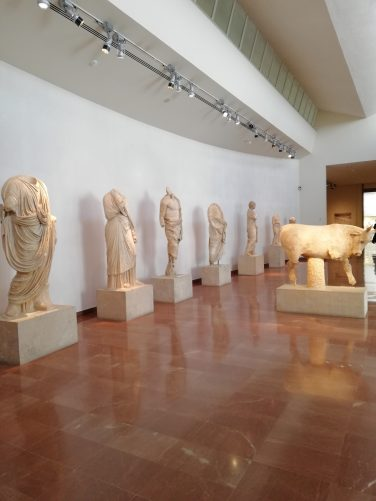 A collection of statues from the Nymphaeum of Herodes Atticus at Olympia. They include a marble bull and a row of human figures.