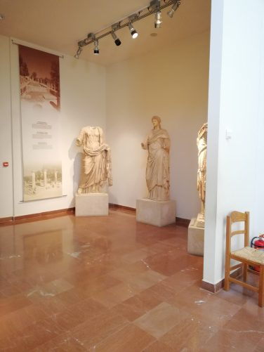Three statues of human figures in a recess. Information on the wall behind indicates these are from the Temple of Hera during the Roman Period.