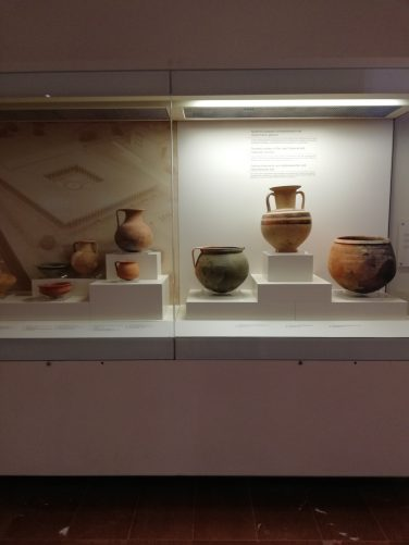 A collection of pots in a display case. They are domestic pottery from the Late Classical and Hellenistic periods.