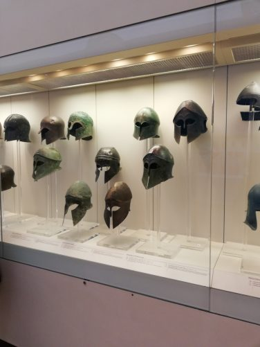 A collection of Corinthian style bronze helmets in a display case.