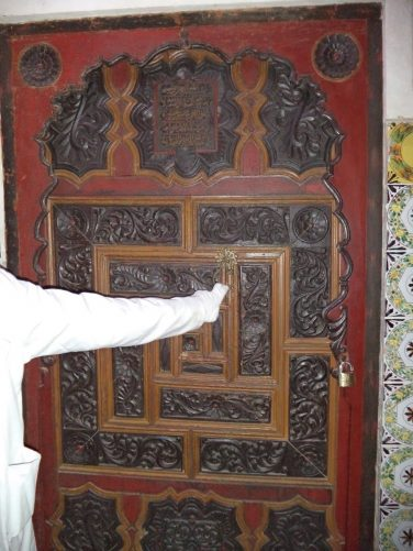 An old decorative door made of cedar wood. The palace has 540 doors made of cedar wood, which are inscribed and engraved with different sculptures and decorations.