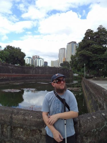 View of a water-filled moat and defensive walls at Intramuros.