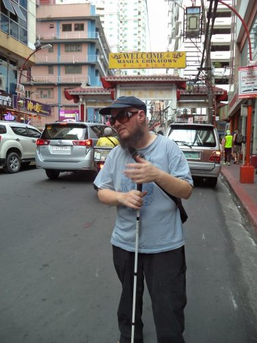 Tony standing in a busy street in Binondo. Another decorative welcome arch in front.