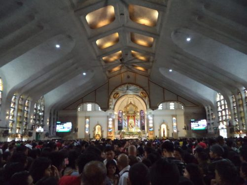 Inside the Minor Basilica of the Black Nazarene looking towards the altar. The basilica is crammed full of people.
