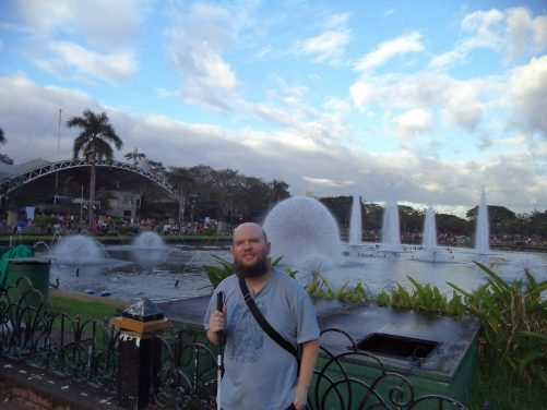 Tony in front of an impressive array of fountains in Rizal Park lake. Many people watching around the edges of the lake.