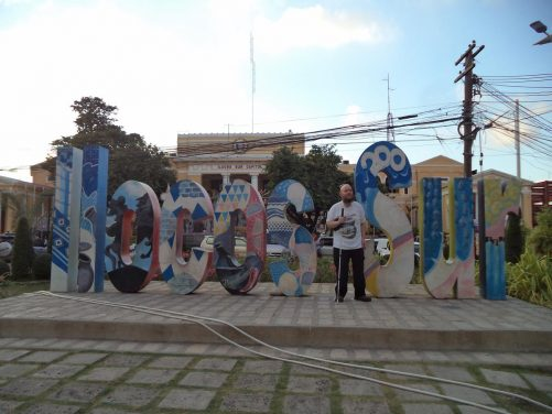 Tony in front of large human-size letters spelling out 'Ilocos Sur', which is the name of the province of which Vigan is capital. In the background, part of the Ilocos Sur Capitol building can be seen. It includes neoclassical style stone columns across an entrance portico.