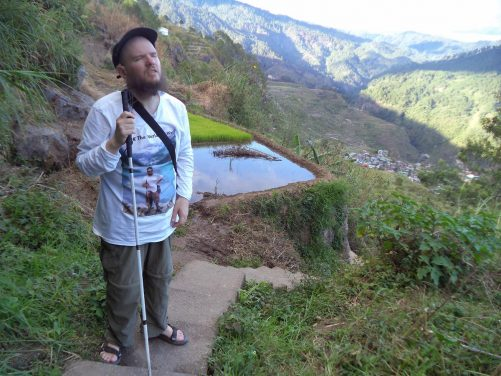 Tony close to a rice terrace. A roughly rectangular pool of water with the rice plants visible.