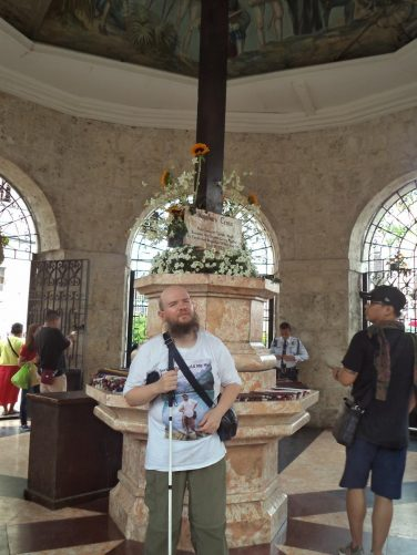 Tony in front of Magellan's Cross, which stands on a marble base in the centre of the building.
