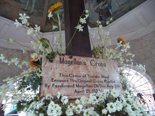 A plaque amongst flowers at the base of the cross. The plaque reads