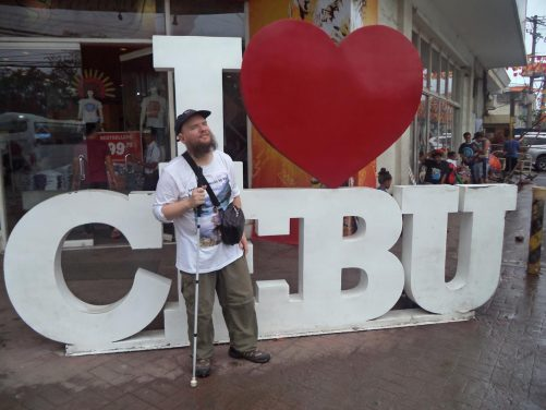 "Tony on Colon Street in front of a sign saying ""I love Cebu"". Allegedly, this is the oldest street in the Philippines. This lively street becomes a market at night."