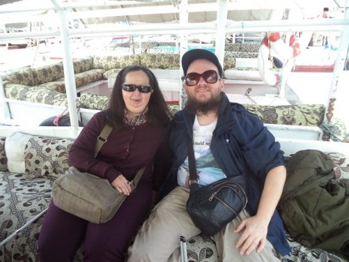 Tatiana and Tony onboard a felucca, a traditional wooden Egyptian sailboat, on the river Nile. The boat is moored with other feluccas visible along side.