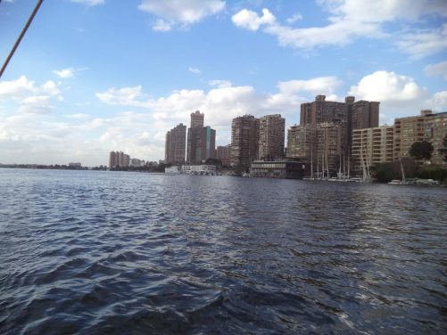 Passing a cluster of tall buildings as the boat passes along the river between Cairo and Giza.