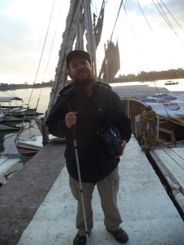 Tony on a jetty with the felucca and other boats moored behind.