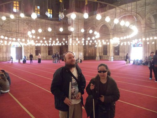 Tony and Tatiana inside the mosque. The interior walls are tiled with alabaster. There is a dome in the centre.