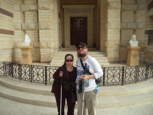 Tony and Tatiana in the entrance porch to a church. A doorway in front. Busts of two Greek Orthodox Patriarchs of Alexandria at either side.