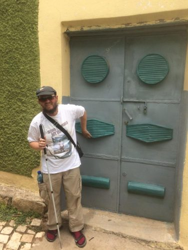 Tony outside another house. The metal door is painted grey and green.
