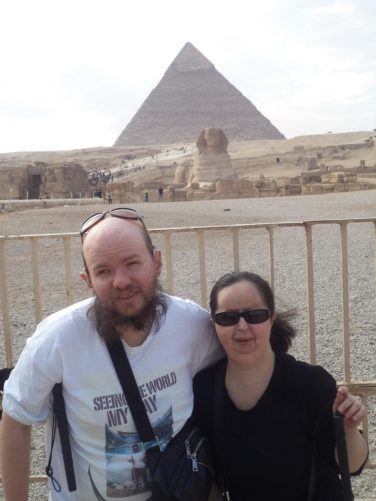 Tony and Tatiana at the edge of the Giza pyramid complex site with Great Sphinx of Giza and the Pyramid of Khafre behind.