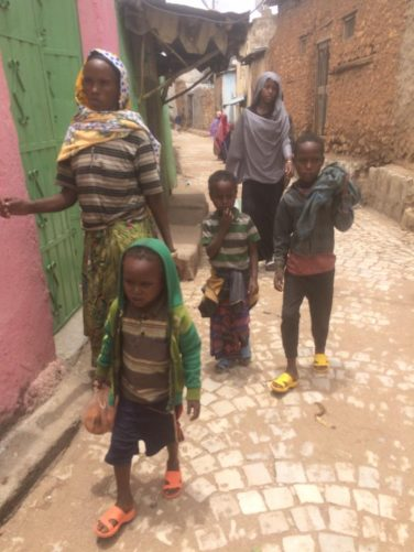 A local woman with three young boys and a girl going about their everyday business in one of Harar's narrow streets.