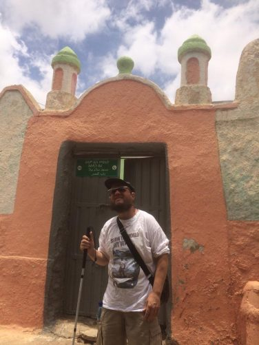 Tony in front of the colourful outer doorway and walls of a small mosque in the walled city.