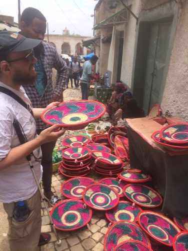 Tony in Mekina Girgir, a street famous for its tailors. Tony holding a brightly coloured woven bowl.