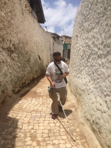 Tony walking along a narrow street between high white-painted walls.