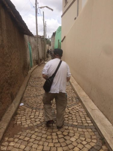 Tony walking along a narrow street between the walls of houses. The ground paved with cobblestones.