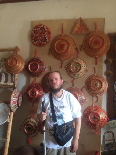 Tony at a Women's Association where they make baskets. A collection of baskets can be seen on the wall behind.