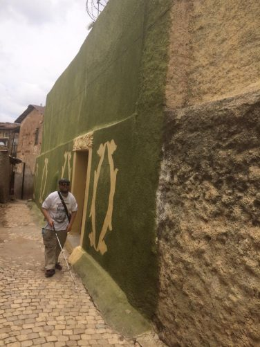 Tony walking past an olive green painted building heading to the Arthur Rimbaud museum.