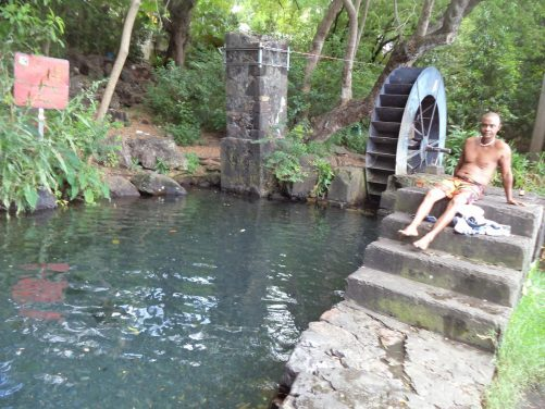 Moulin de la Tour des Roches. A pool of water with a metal waterwheel at the end, part of an old water mill. Surrounded by lush vegetation. Located at Savanna, a part of Saint Paul.