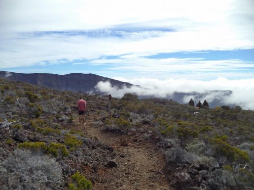 View along a trail near Piton de la Fournaise volcano. Cloud floating over a valley in front.