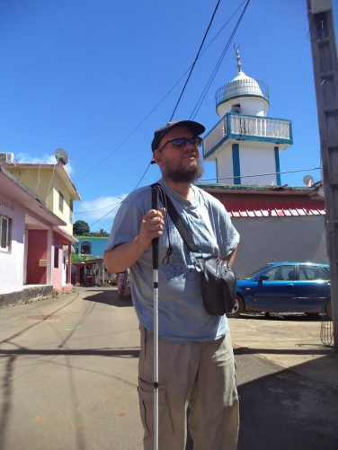 Tony in Sada, a small seaside town on the south-west coast of Grande-Terre. View along a narrow street with the minaret of a mosque painted in blue and white standing behind.