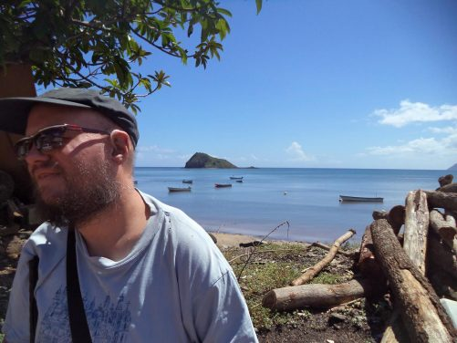 Tony beneath a palm tree on the edge of Sada Beach.