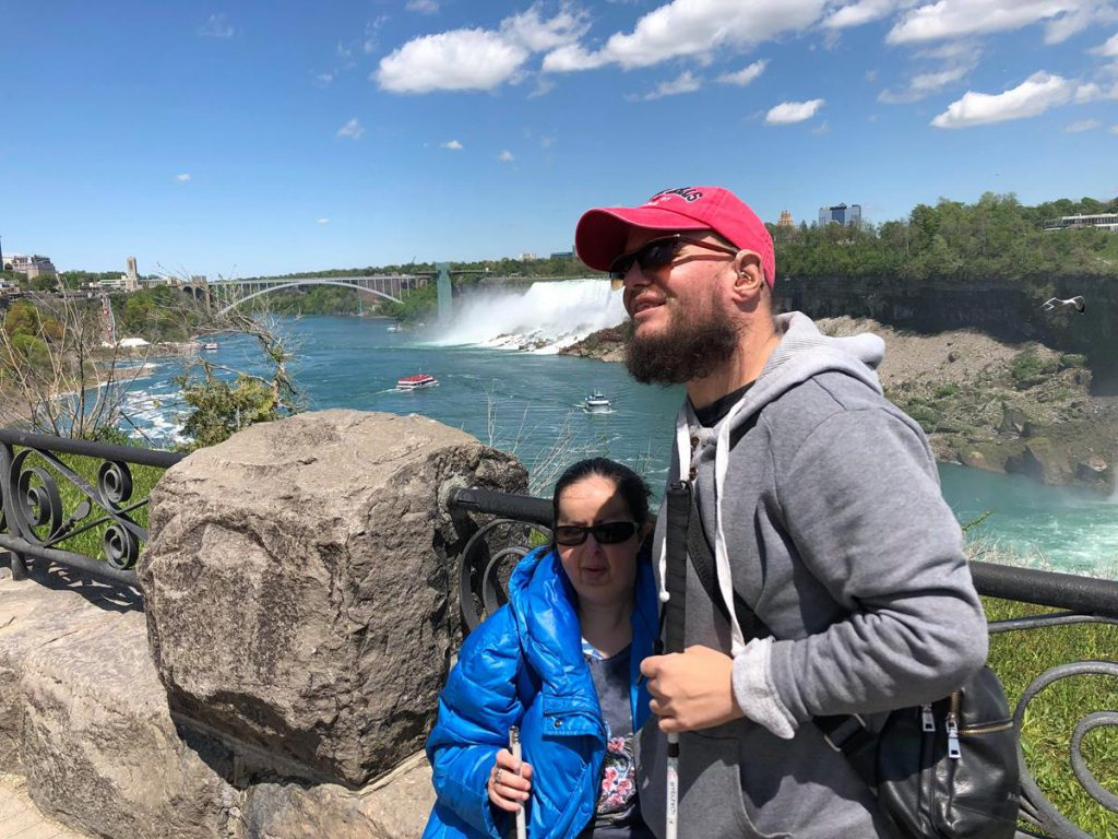 View of the Niagara River with American Falls and Bridal Veil Falls, the other two waterfalls that make up Niagara Falls, visible on the far side. American Falls is 34 metres in height and is located on US side of the border. Tony and Tatiana in the foreground.