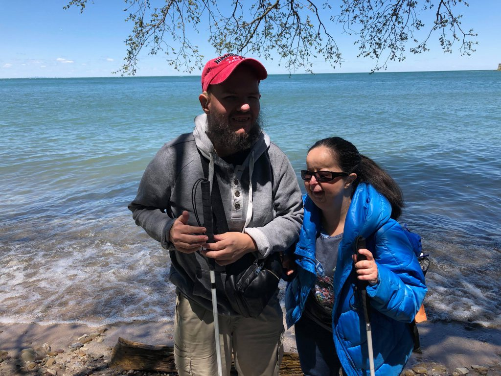 Tatiana and Tony under the shade of a tree at the edge of the lake.