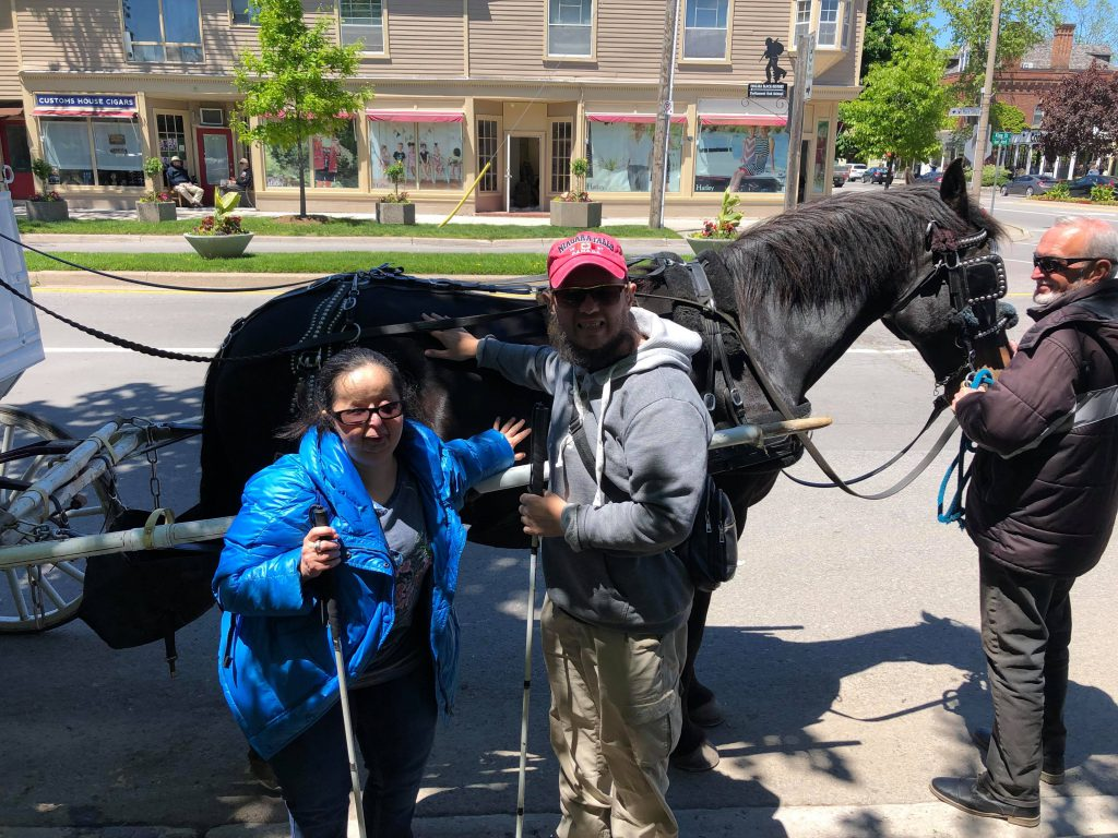 Tatiana and Tony touching a horse which is tethered to a carriage in a street at Niagara-on-the-Lake.