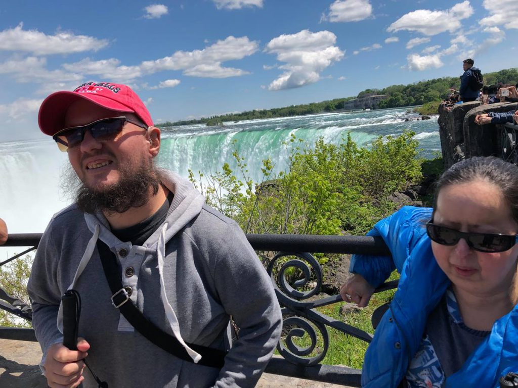 Tony and Tatiana with a dramatic view of Niagara Falls. This is Horseshoe Falls, which at 51 metres is the highest and largest of the three waterfalls that collectively form Niagara Falls. As the name suggests, looking from above, the falls form a horseshoe shape. The falls straddle the border of Canada and the United States.